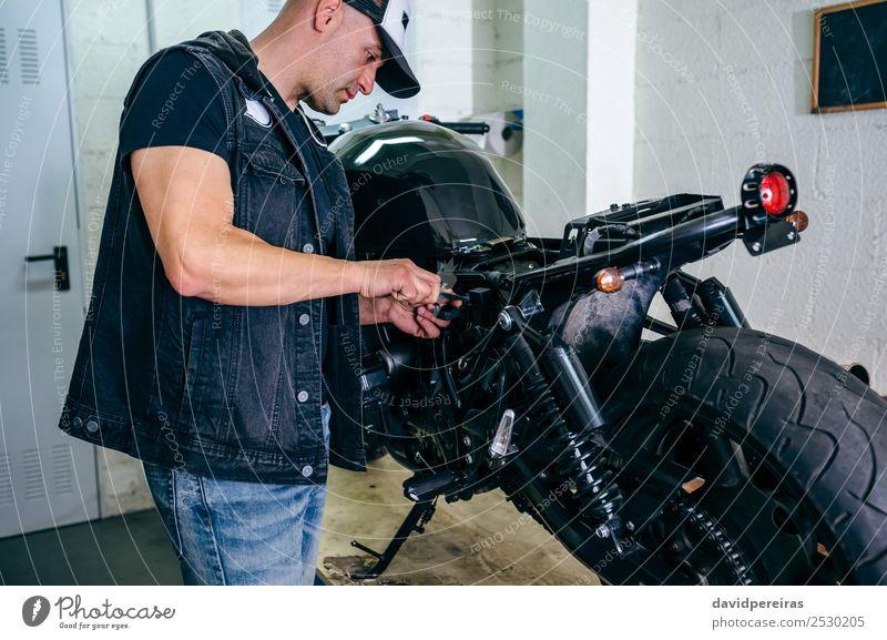 Motorradmechaniker beim Wechseln einer Sicherung Lifestyle Stil Arbeit & Erwerbstätigkeit Mensch Mann Erwachsene Fahrzeug Jeanshose authentisch retro schwarz