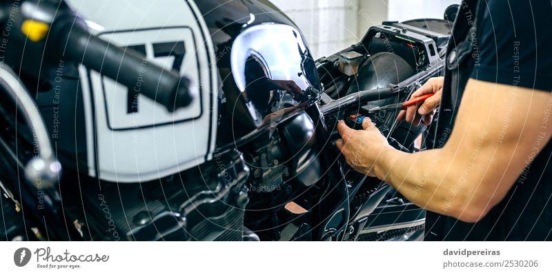 Motorradmechaniker beim Wechseln einer Sicherung Lifestyle Stil Arbeit & Erwerbstätigkeit Mensch Mann Erwachsene Arme Hand Fahrzeug authentisch retro schwarz