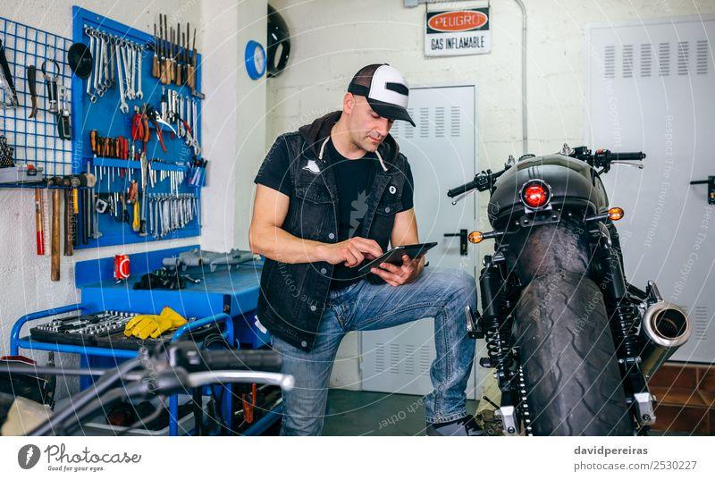 Mechanische Überprüfung von Custom-Motorrädern mit Tablett Lifestyle Stil Arbeit & Erwerbstätigkeit Technik & Technologie Mensch Mann Erwachsene Fahrzeug