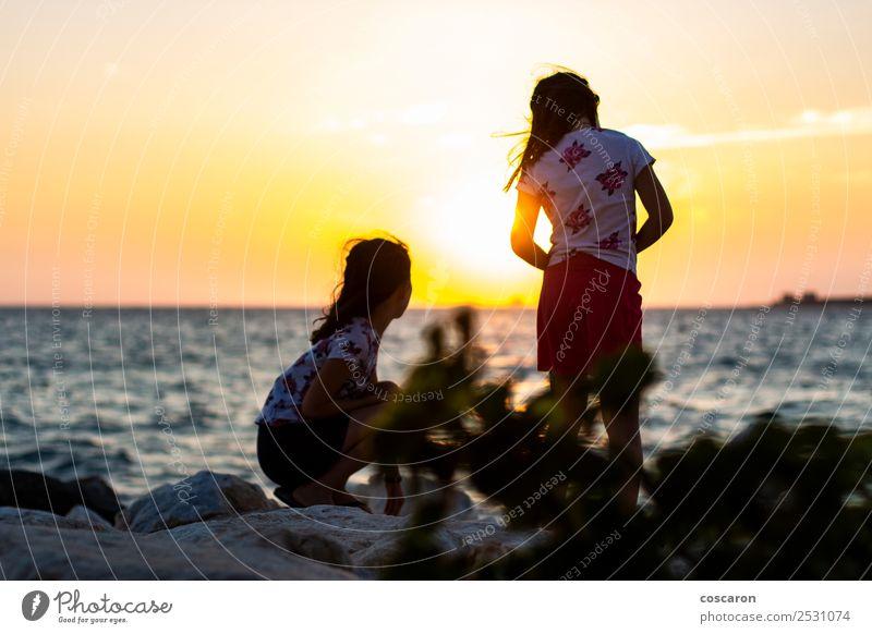 Zwei Mädchen auf dem Breakeater bei Sonnenuntergang Lifestyle Freude Glück schön Erholung Ferien & Urlaub & Reisen Camping Sommer Strand Meer Kind Junge