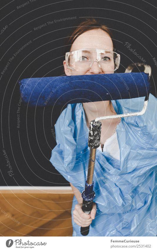 Woman in protective clothes showing a blue paint roller Freizeit & Hobby feminin Frau Erwachsene 1 Mensch 18-30 Jahre Jugendliche 30-45 Jahre Kreativität