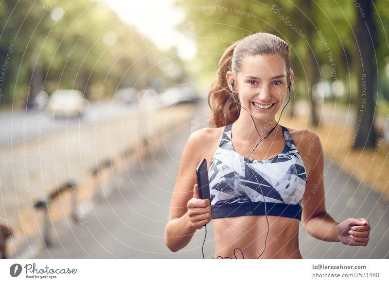 Fit, gesunde, sportliche Frau, die am Flussufer joggt. Lifestyle Sommer Musik Sport Joggen PDA Erwachsene Wärme Park Straße Fitness Lächeln rennen Gesundheit