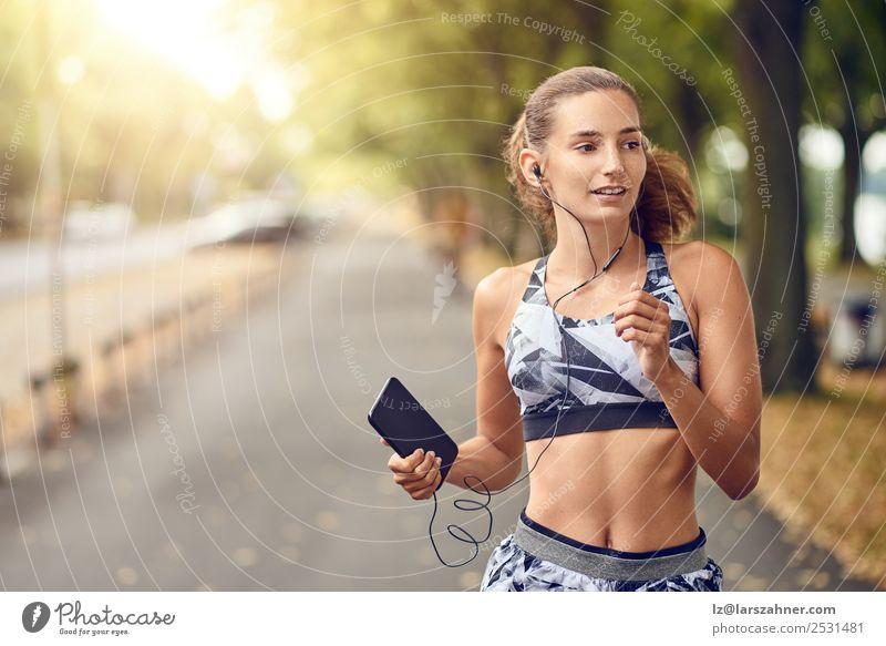 Fit, gesunde, sportliche Frau, die am Flussufer joggt. Lifestyle Sommer Musik Sport Joggen PDA Erwachsene 1 Mensch 18-30 Jahre Jugendliche Wärme Park Straße
