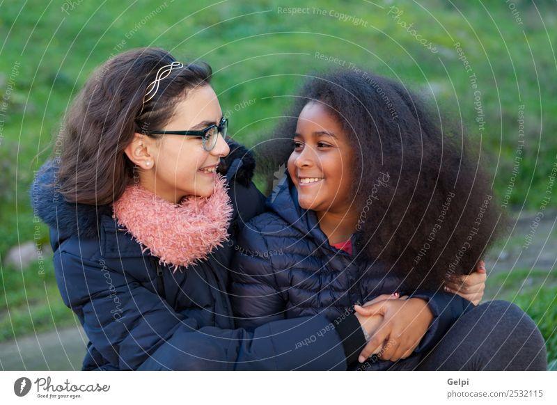 Zwei glückliche Mädchen im Park mit Mänteln. Freude Glück schön Gesicht Winter Kind Mensch Familie & Verwandtschaft Freundschaft Kindheit Gras Mantel Schal