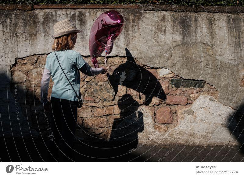 Mädchen mit Delfin-Luftballon wirft einen Schatten an die Mauer Spielen Jahrmarkt Mensch feminin Kindheit 1 Wand Hut Delphine Spielzeug beobachten Blick
