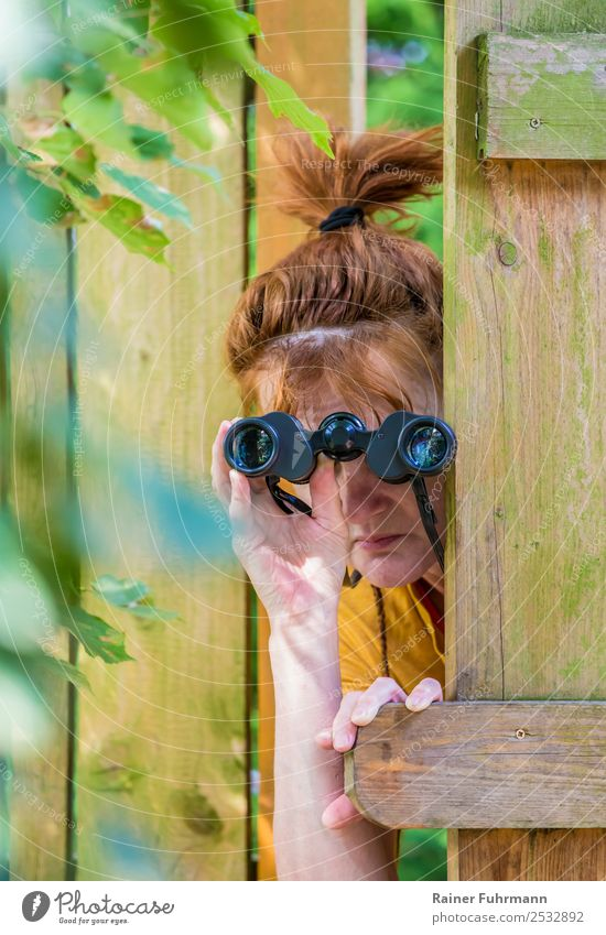 """eine neugierige Frau beobachtet mit einem Fernglas Mensch feminin Erwachsene Kopf 1 Umwelt Garten Zaun beobachten Neugier Wachsamkeit Neid """"Fernglas"""