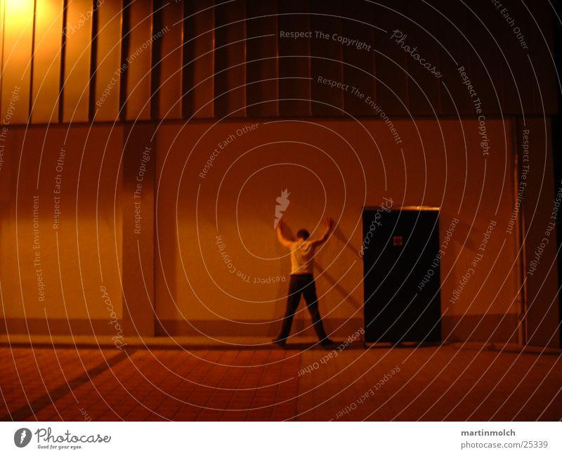 An der Wand rot Haus Bordsteinkante Mann stehen Nacht Licht dunkel Stimmung Abdeckung Parkplatz Architektur Tür Mensch verhaftet durchsuchung Abend Schatten