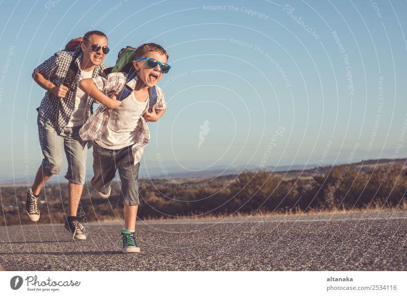 Vater und Sohn laufen auf der Straße in der Tageszeit. Konzept des Tourismus. Lifestyle Freude Glück Freizeit & Hobby Ferien & Urlaub & Reisen Ausflug Abenteuer