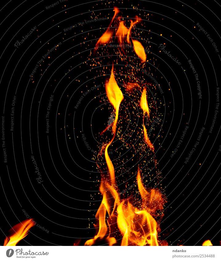 gelbe Flammen mit aufflackernden Funken Wärme Bewegung leuchten dunkel heiß hell rot schwarz Energie Farbe Hintergrund Freudenfeuer Brandwunde Feuerstelle Kohle