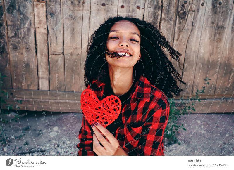 Fröhliche junge Frau mit einem roten Herzen Lifestyle Stil Design Freude Haare & Frisuren Gesundheit Wellness harmonisch Mensch feminin Junge Frau Jugendliche