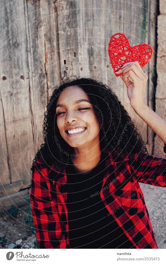 Fröhliche junge Frau, die ein rotes Herz hält. Lifestyle Stil Design Freude schön Gesundheit Wellness Wohlgefühl Zufriedenheit Mensch feminin Junge Frau