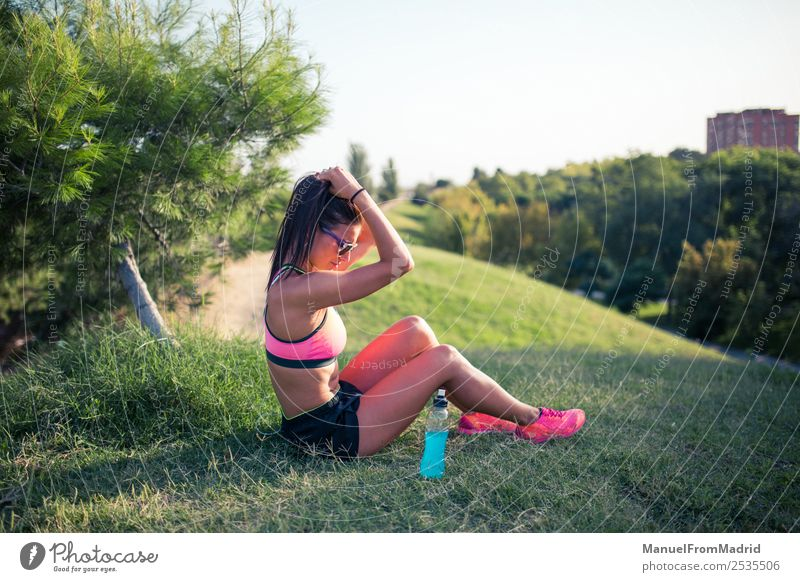athletische Frau, die sich ausruht Flasche Lifestyle schön Sommer Sport Erwachsene Natur Park Fitness sitzen Energie Training Läufer aussruhen