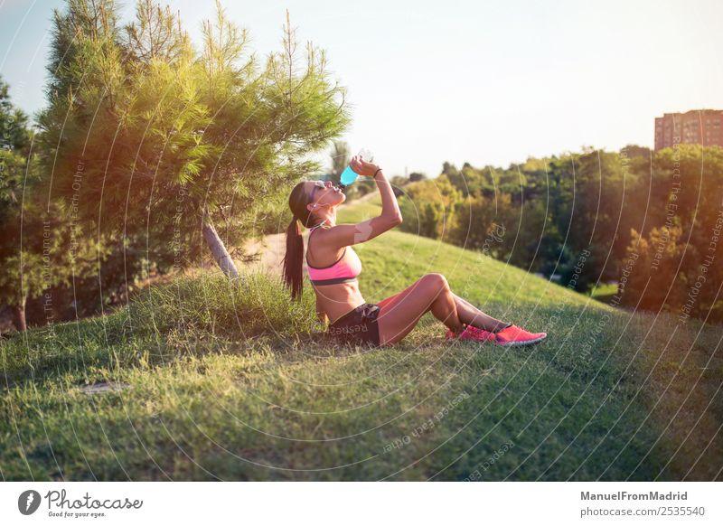sportliche Frau, die sich ausruht und trinkt trinken Flasche Lifestyle schön Sommer Sport Erwachsene Natur Park Fitness sitzen Energie Training Läufer