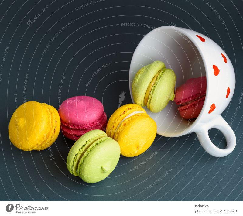 Makronen in einem weißen Keramikbecher Dessert Becher hell gelb rosa rot schwarz Farbe Macaron Tasse Hintergrund Lebensmittel farbenfroh Vanille Französisch