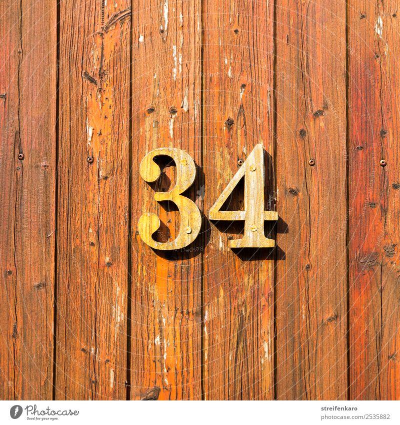 Holzziffern 34 auf einer der Tür aus Holzlatten Wohnung Haus Hausnummer Gebäude Ziffern & Zahlen Zeichen ästhetisch braun gelb Design Handwerk Farbfoto