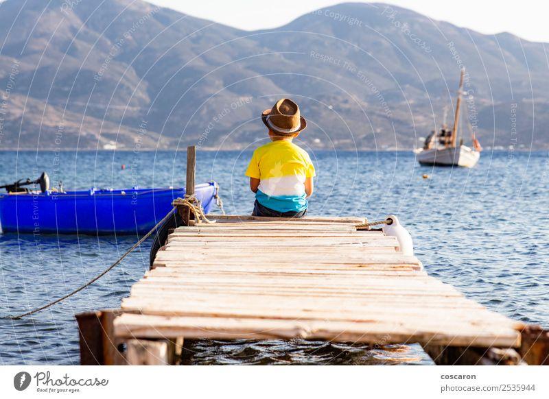 Kleiner Junge auf einem Dock, der auf dem Rücken sitzt und auf den Ozean schaut. Lifestyle Freude Glück Freizeit & Hobby Ferien & Urlaub & Reisen Sommer Strand