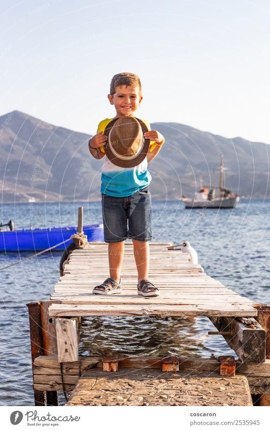 Porträt eines kleinen Kindes auf einem Dock mit einem Hut in der Hand. Lifestyle Glück schön Erholung Freizeit & Hobby Ferien & Urlaub & Reisen Sommer Strand