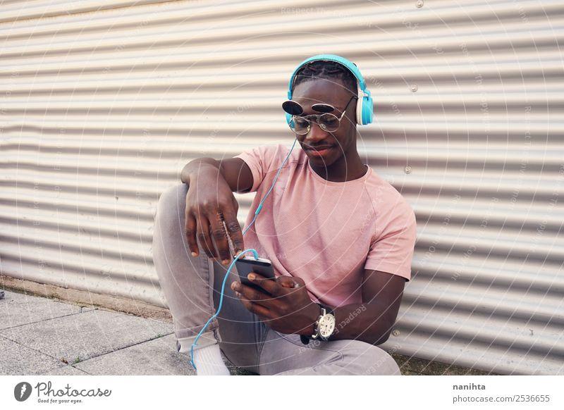Junger Mann hört Musik und benutzt sein Smartphone. Lifestyle Stil Design Freude Freizeit & Hobby Freiheit Handy Headset PDA Kopfhörer Technik & Technologie