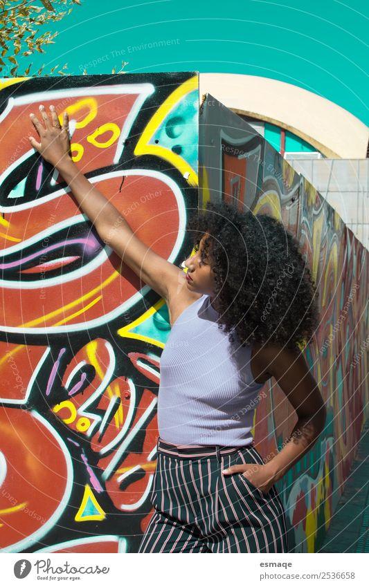 Porträt einer urbanen Frau mit Graffiti Lifestyle exotisch Freude schön feminin Junge Frau Jugendliche Mode Afro-Look Abenteuer Gefühle Gelassenheit Identität