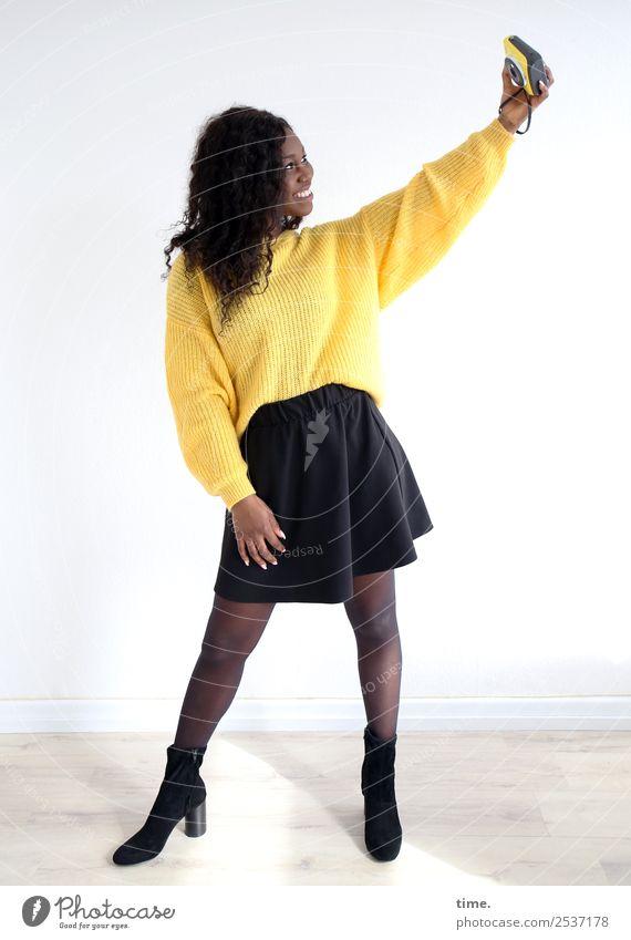 Apolline Raum feminin Frau Erwachsene 1 Mensch Medien Fotokamera Rock Pullover Stiefel brünett langhaarig Locken festhalten lachen Blick stehen Fröhlichkeit