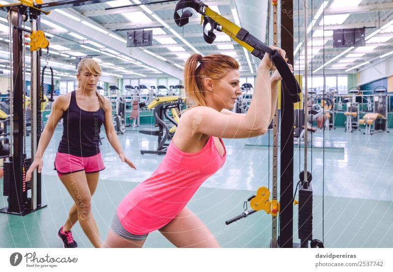 Personal Trainerin, die der Frau im Suspensionstraining hilft. Lifestyle schön Körper Sport Arbeit & Erwerbstätigkeit Erwachsene Fitness authentisch muskulös