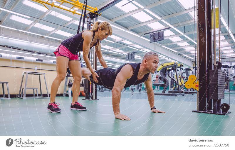 Personal Trainer, der den Mann im Suspensionstraining unterrichtet. Lifestyle schön Körper Sport Arbeit & Erwerbstätigkeit Frau Erwachsene Fitness authentisch