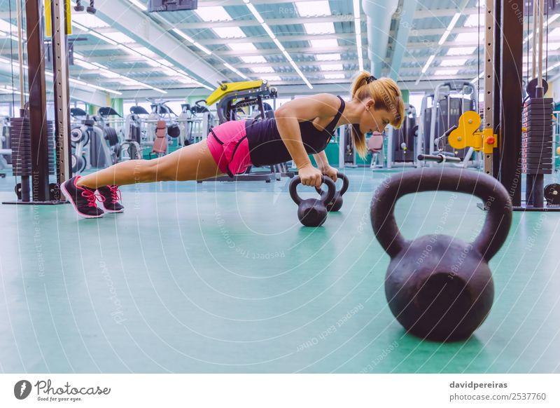 Frau beim Pushup über Kettlebells im Crossfit-Training Lifestyle Körper Club Disco Sport Erwachsene Fitness authentisch muskulös stark schwarz Kraft Liegestütze