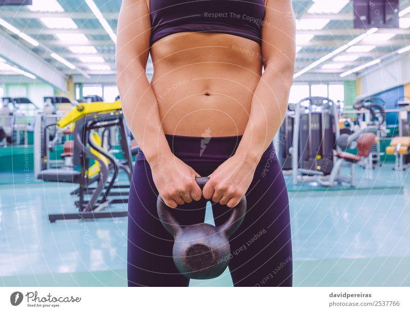 Frau mit schmaler Taille und schwarzer Sportbekleidung mit Kugelkopf. Diät schön Körper Mensch Erwachsene Fitness authentisch dünn Erotik Kraft Kettlebell