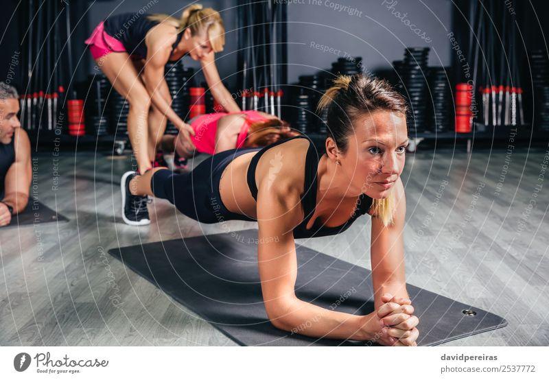 Frau macht Liegestütze mit Trainer im Hintergrund Glück Körper Sport Schule Erwachsene Mann Arme Menschengruppe Fitness authentisch muskulös stark Kerngehäuse