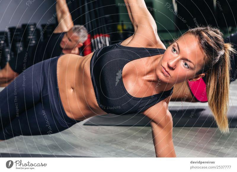 Blonde Frau bei Übungen im Fitnessstudio Glück Körper Sport Schule Erwachsene Mann Arme Menschengruppe authentisch muskulös stark üben Sporthalle Dehnung