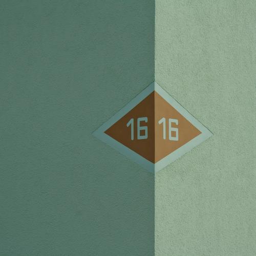 16 Haus Fassade braun grau Hausnummer Pfeil Wand Mauer Putz Putzfassade Lichtseite Schattenseite Grenze rechts links Ecke Dreieck Ziffern & Zahlen 1616 Linie