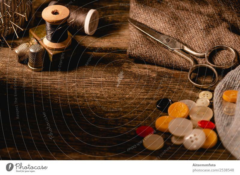 Nahaufnahme der hölzernen Nähspule und der Knöpfe auf dem Holztisch Freizeit & Hobby Tisch Arbeitsplatz Handwerk Werkzeug Schere Accessoire Metall hell schwarz