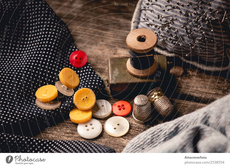 Nahaufnahme der hölzernen Nähspule und der Knöpfe auf dem Holztisch Freizeit & Hobby Tisch Arbeitsplatz Handwerk Werkzeug Stoff Accessoire Metall schwarz