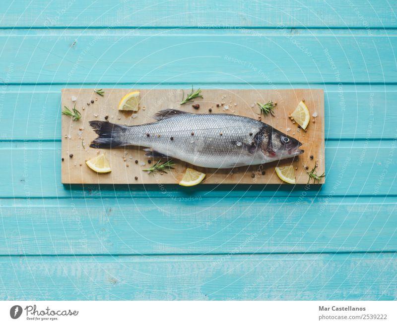 Seebarsch auf Küchentisch mit Zitrone und Rosmarin Meeresfrüchte Kräuter & Gewürze Essen Abendessen Diät Tisch Restaurant Tier Holz schreiben frisch lecker blau