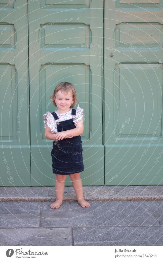 Mädchen klein Kleid Tür feminin 1 Mensch 1-3 Jahre Kleinkind Kleinstadt Altstadt Haus Kord blond Locken Pony beobachten Lächeln Freundlichkeit niedlich blau