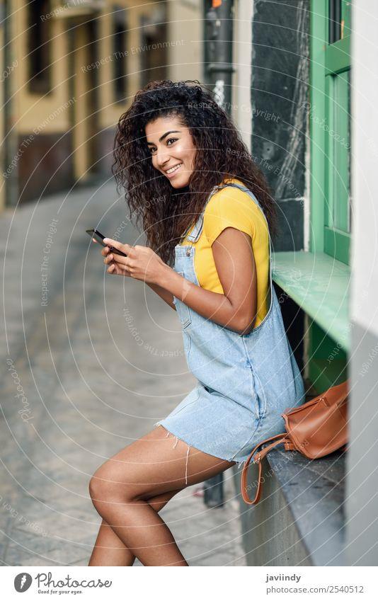 Afrikanische Frau, die mit ihrem Smartphone schreibt. Lifestyle Stil Glück schön Haare & Frisuren Telefon PDA Technik & Technologie Mensch feminin Mädchen