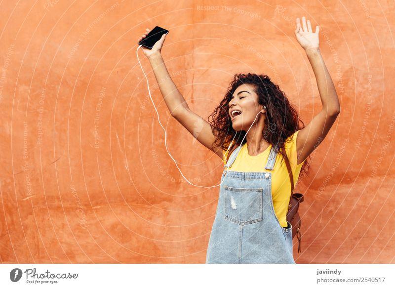 Glückliches arabisches Mädchen beim Musikhören und Tanzen Lifestyle Stil schön Haare & Frisuren Telefon PDA Technik & Technologie Mensch feminin Junge Frau