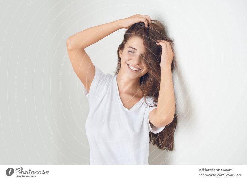 Junge lächelnde blonde Frau, die sich an die Wand lehnt. Lifestyle Glück schön Körper Haut Gesicht Schminke Behandlung Erwachsene 1 Mensch 18-30 Jahre