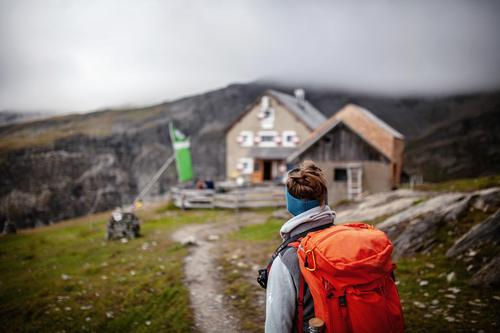 Hütte in Sicht Frau Erwachsene wandern Hohen Tauern NP Bergsteiger Bergsteigen Hüttenferien Holzhütte Berge u. Gebirge Rucksack Rucksacktourismus Pause kommen