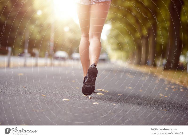 Junge Frau beim Joggen auf einer Herbststraße Lifestyle Erholung Sommer Sonne Sport Mensch Erwachsene Fuß Straße Schuhe Fitness hinten rennen Beine Winkel