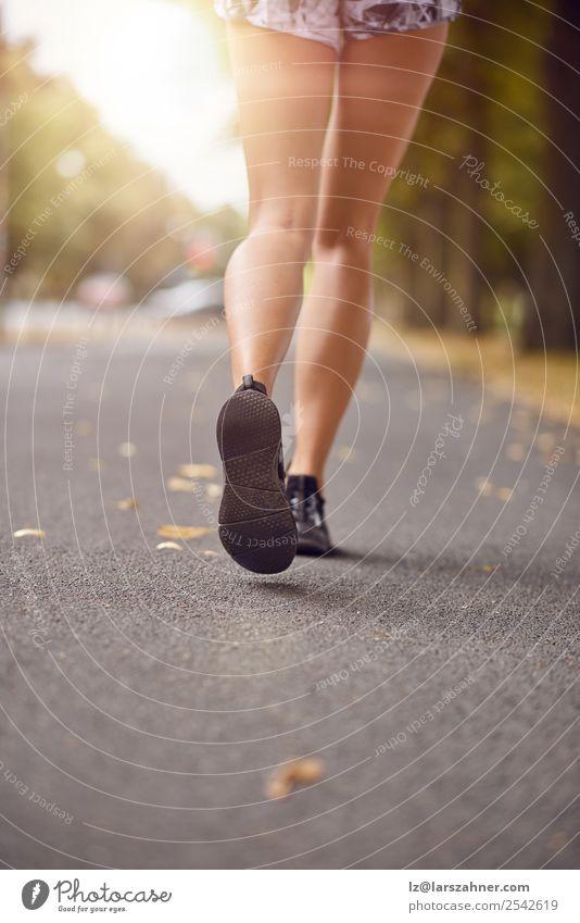 Junge Frau beim Joggen auf einer Herbststraße Lifestyle Erholung Sommer Sonne Sport Mensch Erwachsene Fuß 1 18-30 Jahre Jugendliche Straße Schuhe Fitness hinten