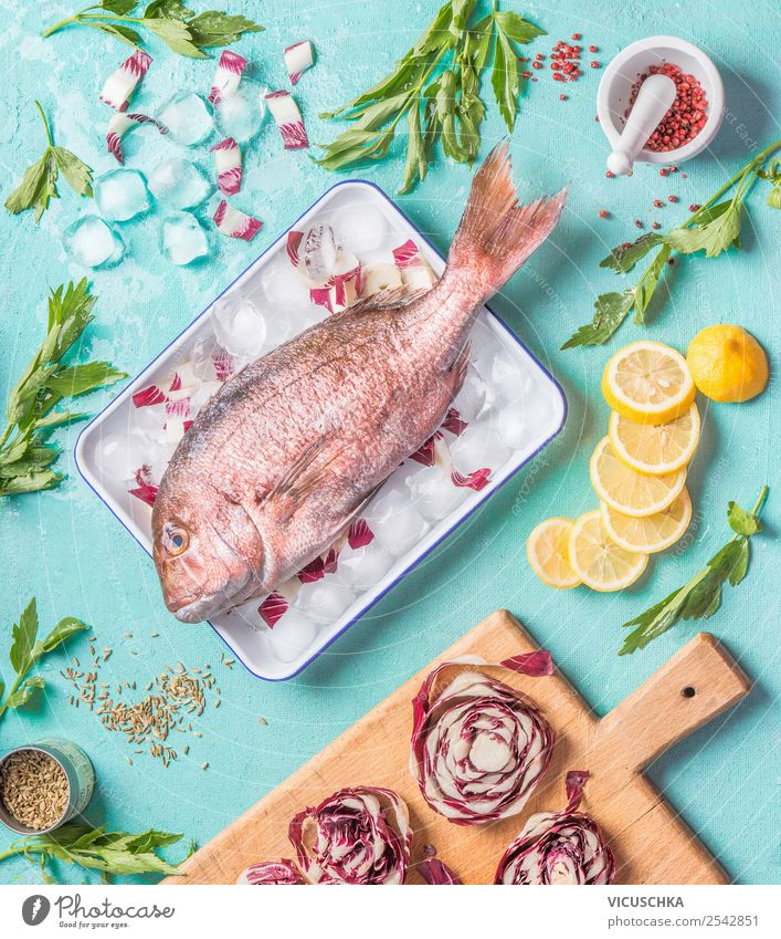 Dorado Fisch auf Küchentisch mit Zutaten Lebensmittel Kräuter & Gewürze Öl Ernährung Mittagessen Abendessen Bioprodukte Vegetarische Ernährung Diät Geschirr
