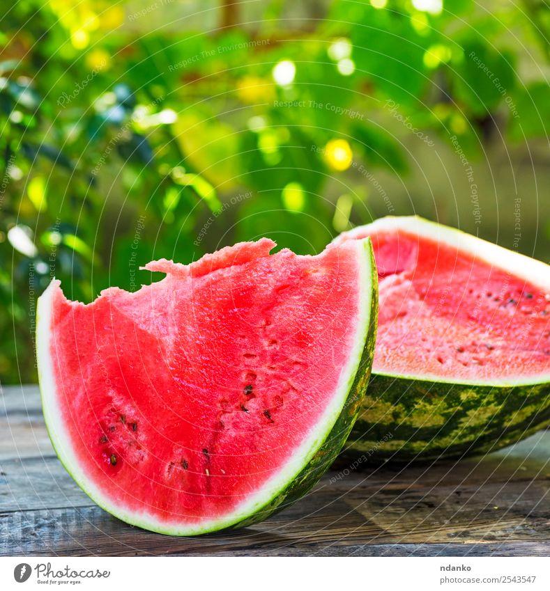 eine reife Wassermelone schneiden Frucht Ernährung Vegetarische Ernährung Tisch Natur Holz Essen frisch natürlich saftig grün rot Farbe Hintergrund Scheibe