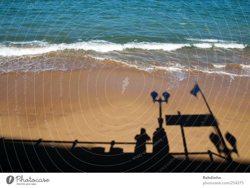 standing on the shadows of beachtown Mensch Natur Wasser blau Sonne Ferien & Urlaub & Reisen Sommer Meer Strand schwarz gelb Sand Küste Lampe Wellen