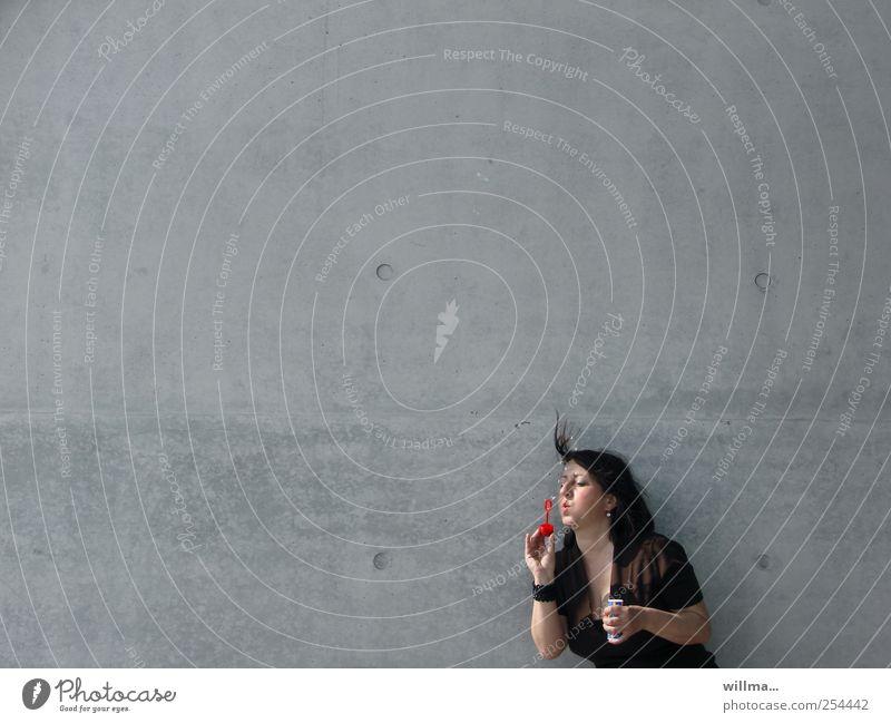 frau bläst mit hingabe seifenblasen vor neutralem hintergrund Frau Erwachsene 1 Mensch Mauer Wand brünett Spielen grau Leichtigkeit Seifenblase einzeln