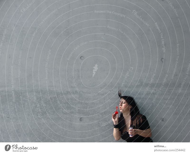 seifenblaseninslochzielpusten Mensch Frau Erwachsene Wand Spielen grau Mauer Fassade Beton einzeln brünett blasen Seifenblase Leichtigkeit Kinderspiel 30-45 Jahre