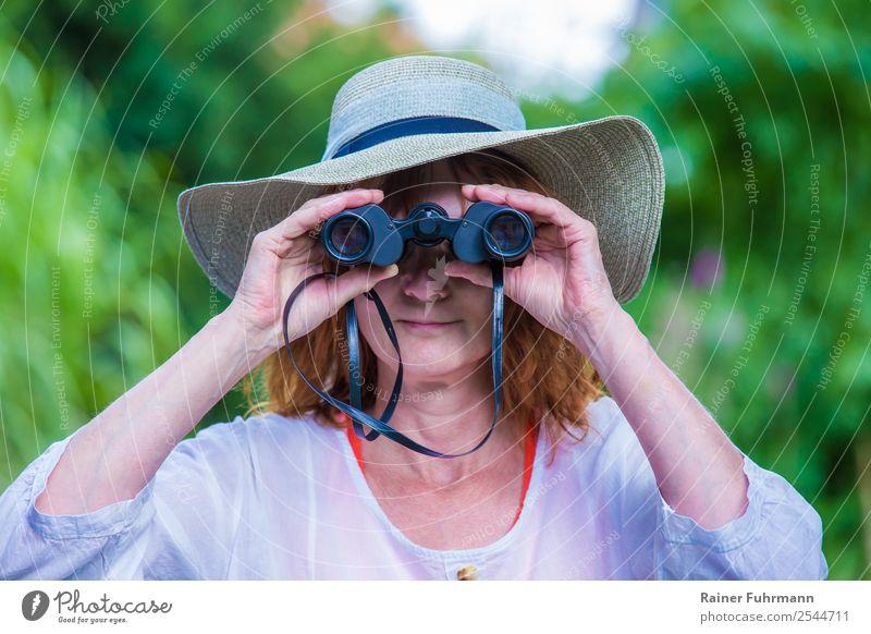 """eine Frau mit Hut blickt durch ein Fernglas Mensch feminin Erwachsene 1 beobachten Blick Freundlichkeit Neugier """"Frau Fernglas,"""" Farbfoto Außenaufnahme Tag"""
