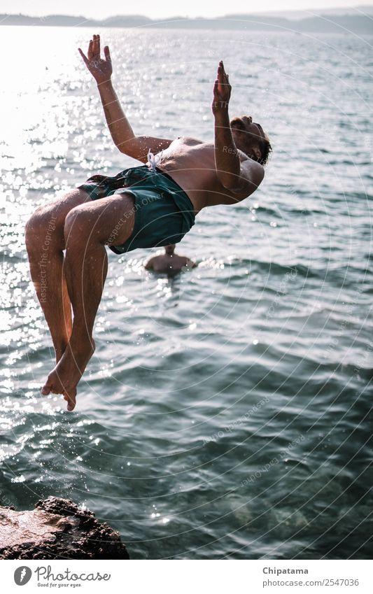 Mann, der an einem Strand zurückspringt. Wasser Freude MEER Sand Rückwärtssalto Sommer Erholung Freiheit Ferien & Urlaub & Reisen Aktion Artist Brandung Glück
