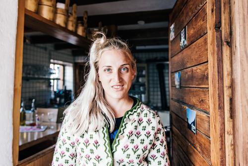 Junge Frau in Almhütte Stil feminin Jugendliche 18-30 Jahre Erwachsene Hütte Tracht Strickjacke blond langhaarig Arbeit & Erwerbstätigkeit Lächeln lachen