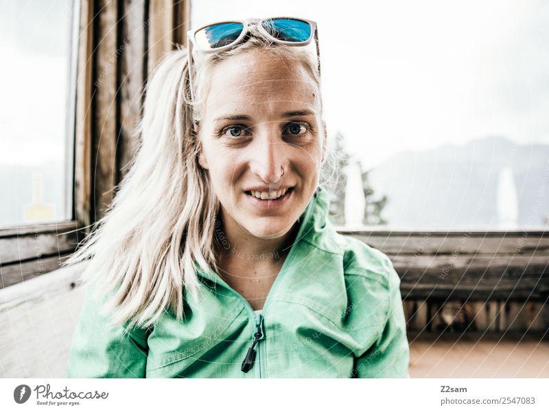 Junge Frau in einer Berghütte Lifestyle wandern Umwelt Natur Landschaft Sommer Schönes Wetter Alpen Berge u. Gebirge Trainingsjacke Sonnenbrille blond Zopf